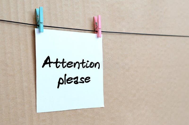 请注意 笔记在垂悬的一个白色贴纸被写 免版税图库摄影