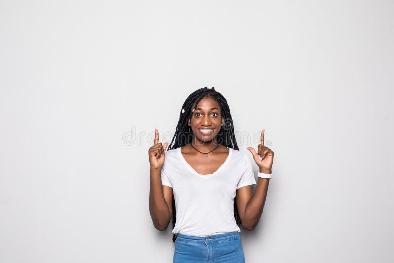 请看那 微笑美丽的年轻非洲的妇女指向和,当站立反对白色背景时 库存照片