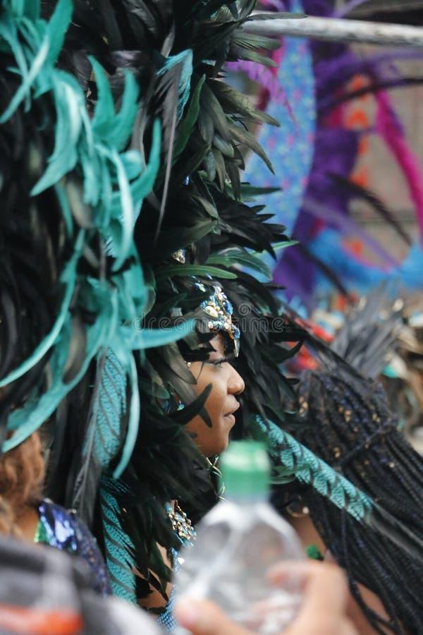 诺丁山,伦敦- 2018年8月27日:诺丁山狂欢节,边在的妇女佩带在parad的观点大羽毛似戴头受话器 库存图片