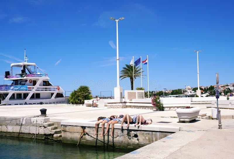 诺瓦利亚,克罗地亚, 2018年6月23日 说谎在江边的四个女孩在诺瓦利亚, Pag,克罗地亚海岛  免版税库存照片
