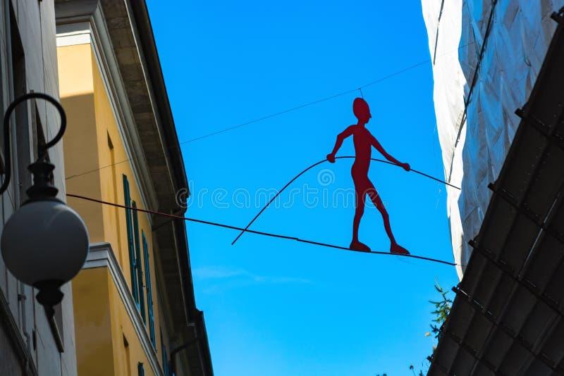 诺瓦腊,意大利- 2016年10月18日:安装现代剪影equilibrist反对天空 库存图片