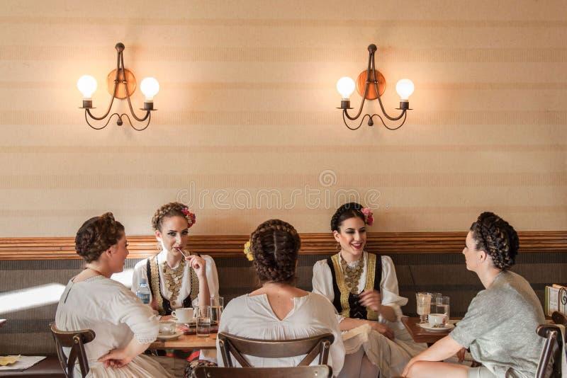 诺维萨德,塞尔维亚- 2017年6月11日:穿一套传统塞尔维亚服装的少妇喝一杯在一个地方咖啡馆 库存图片