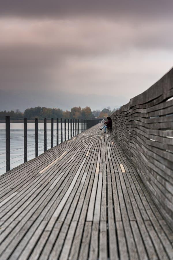 读'Landbote'地方报刊的中年妇女在导致Hurden的著名木板走道的一条长凳 免版税图库摄影