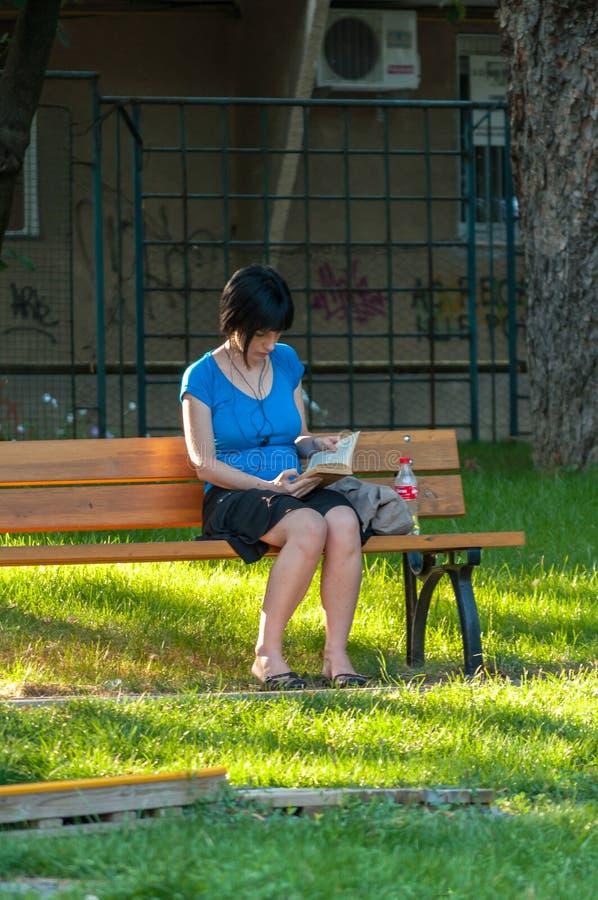 读一本书的妇女在公园 免版税库存图片
