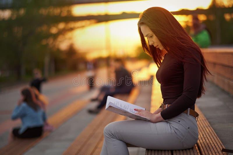 读一本书的年轻亚裔妇女在晚上在日落 r 库存图片