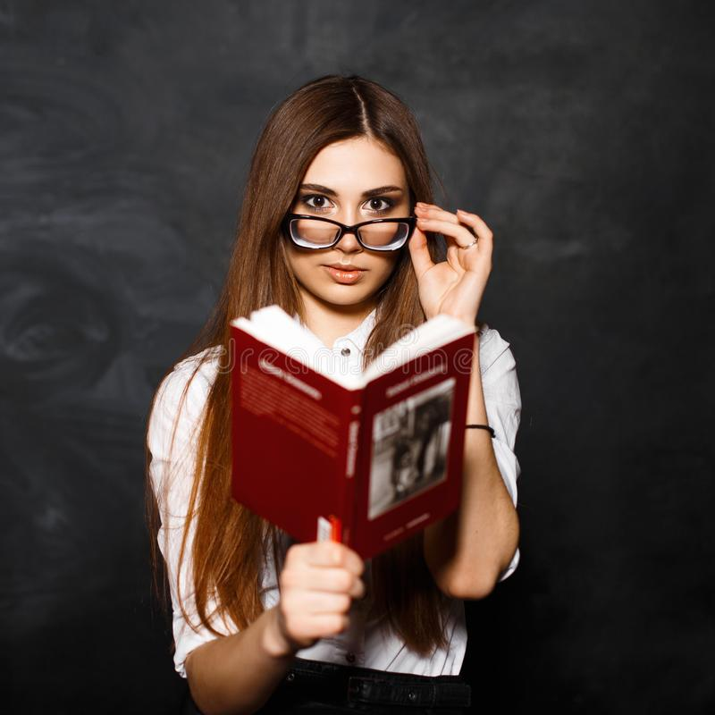 读一本书的年轻美丽的女孩在演播室在黑暗后面 免版税库存照片