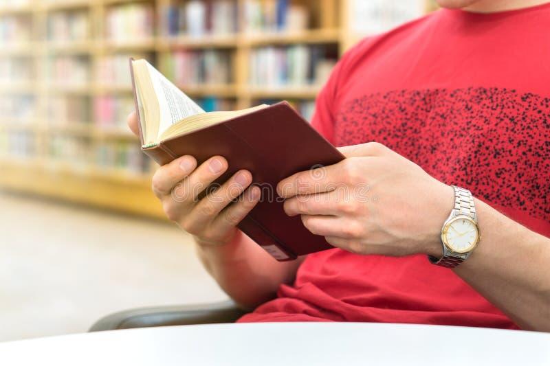 读一本书的年轻运动人或学生在公众或学校 图库摄影