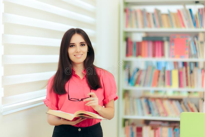 读一本书的老师在学校图书馆里 库存照片
