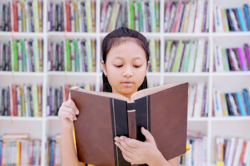 读一本书的聪明的女小学生在图书馆里 免版税库存照片