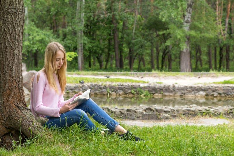 读一本书的逗人喜爱的少年女孩在城市公园 免版税库存照片