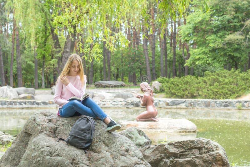 读一本书的逗人喜爱的少年女孩在城市公园 免版税图库摄影
