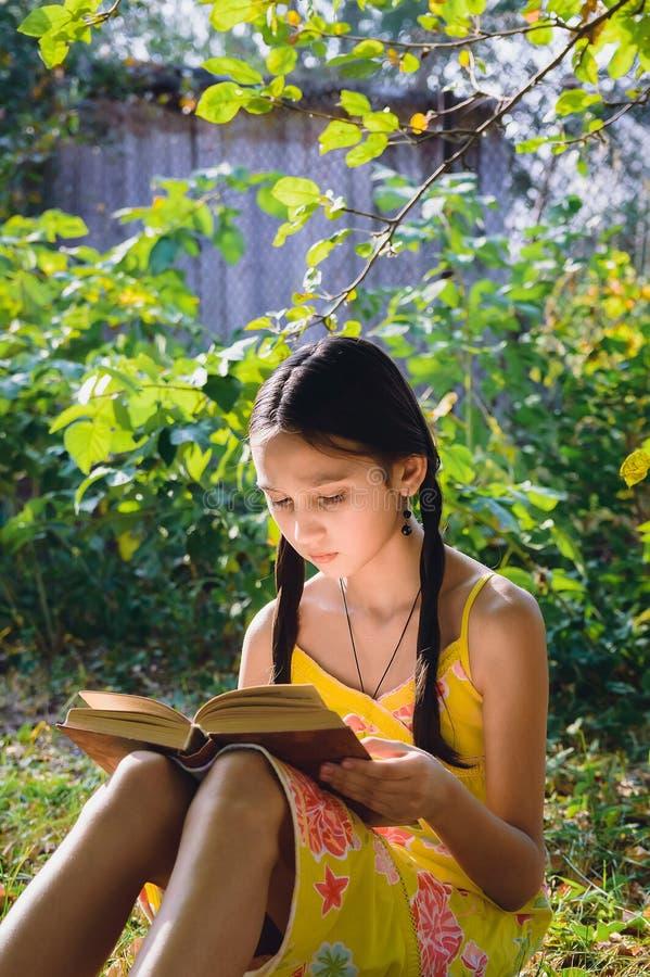读一本书的青少年的女孩在庭院里 免版税库存照片