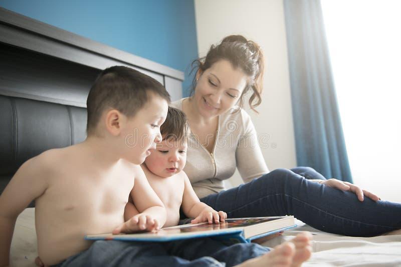 读与她的两childs男孩的母亲一本书在卧室 库存照片