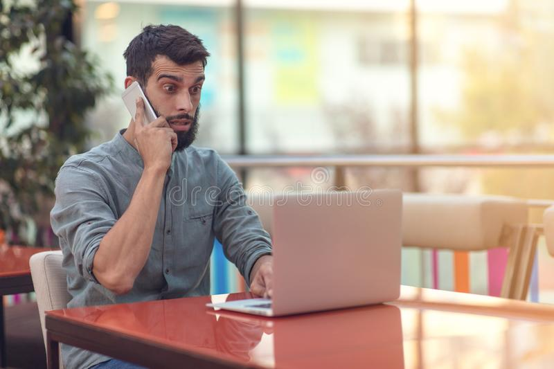 读与结果的激动的愉快的有胡子的自由职业者电子邮件关于在坐在膝上型计算机的现代网上比赛的胜利 免版税库存图片