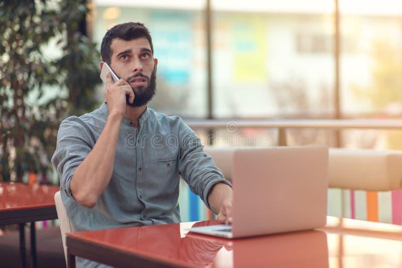 读与结果的激动的愉快的有胡子的自由职业者电子邮件关于在坐在膝上型计算机的现代网上比赛的胜利 免版税库存照片
