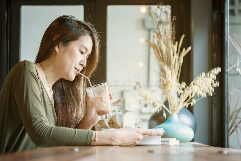 读书和喝被冰的巧克力的特写镜头亚裔妇女在咖啡店的木逆书桌与愉快的面孔在blurre 免版税库存照片
