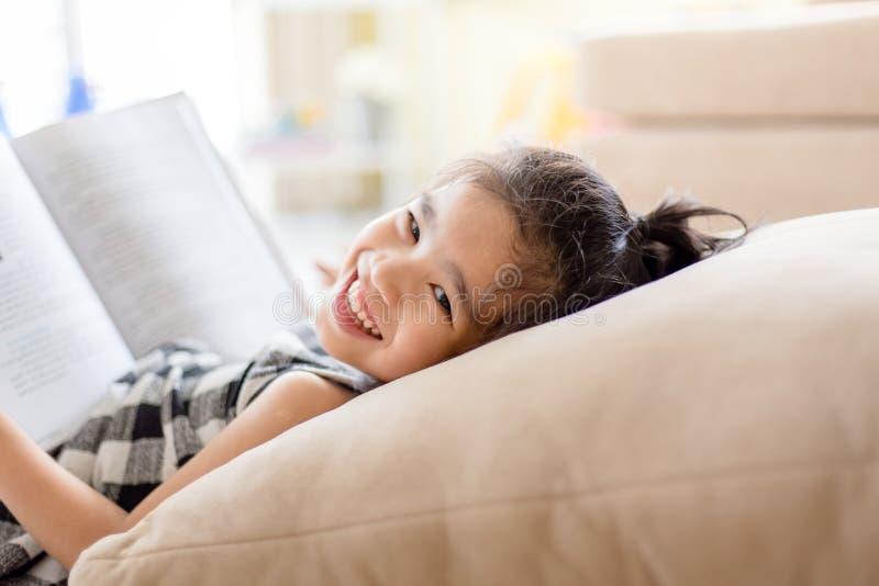 读书和微笑的牙白色的逗人喜爱的亚裔女孩,当在活跃室时 免版税库存图片