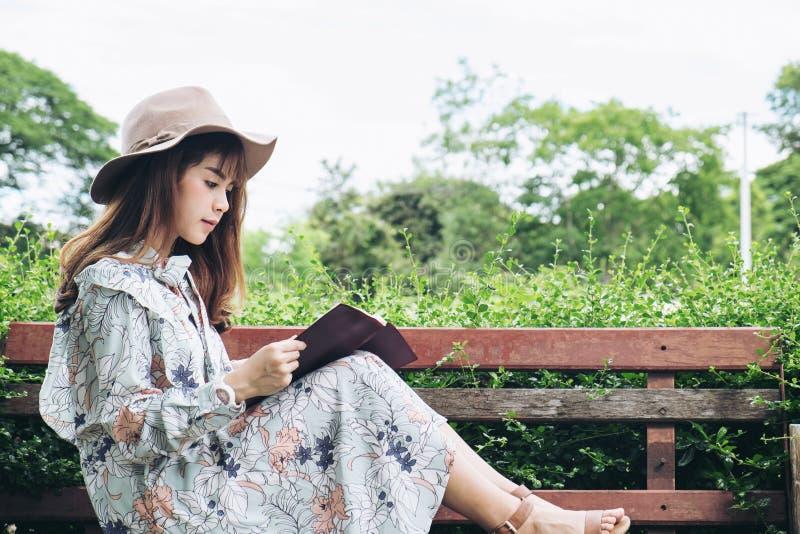 读书和放松在公园的可爱的亚裔妇女 图库摄影