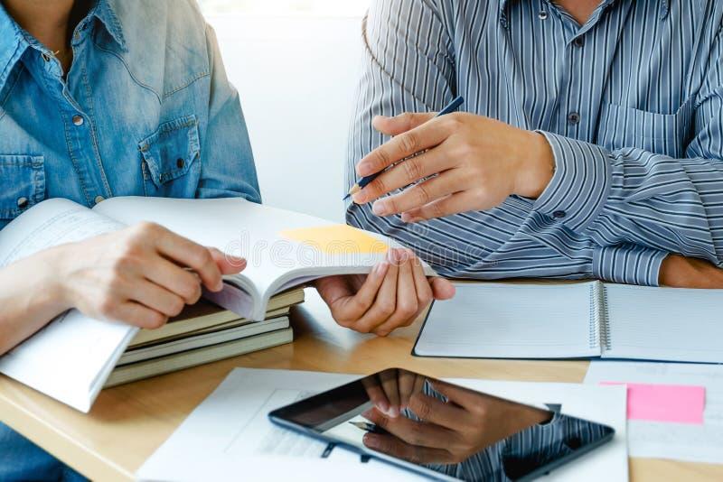 读书或一起做家庭作业的两名确信的学生,当坐在家时 库存图片
