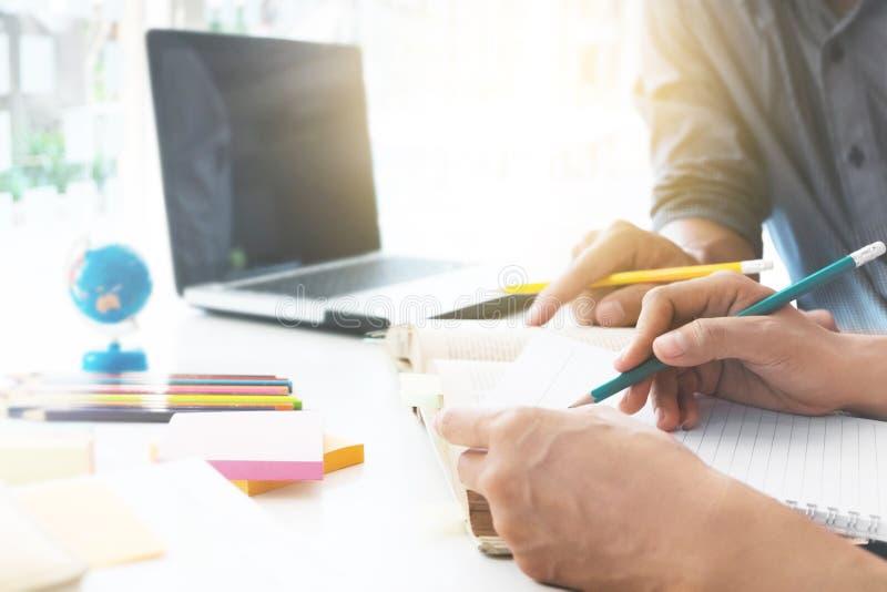 读书或一起做家庭作业的两名确信的学生,当坐在桌上时 库存照片
