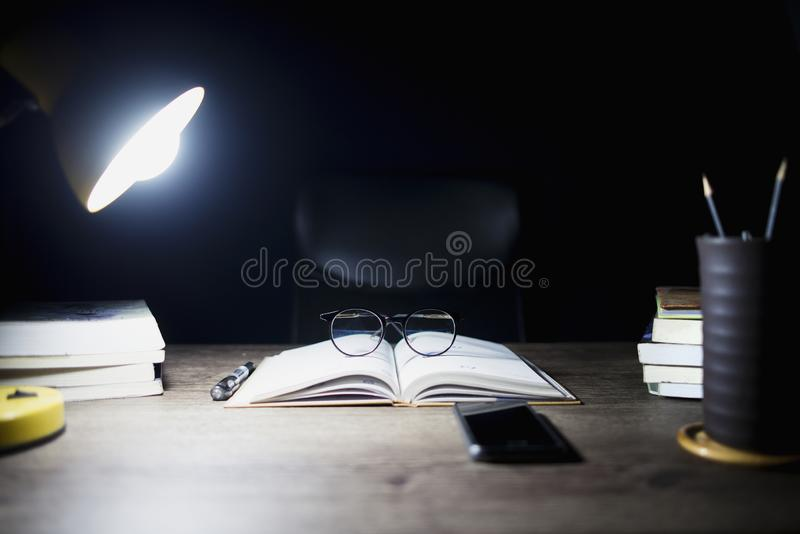 读书桌在夜、开放书和玻璃里安置了,书分部和照明设备灯 图库摄影