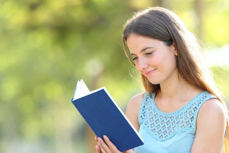 读书的严肃的妇女在绿色背景 免版税库存图片