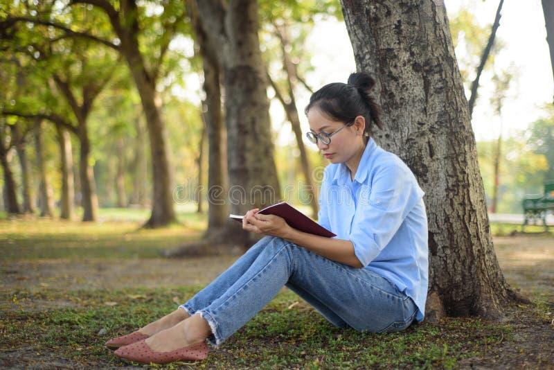 读书的亚裔妇女在树下在庭院里 库存照片