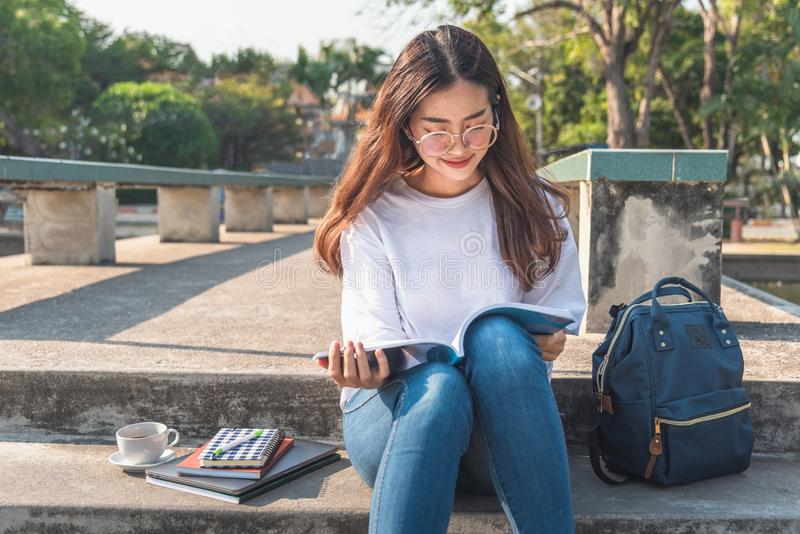 读书的俏丽的轻松的年轻女人在有太阳发光的草坪 库存照片