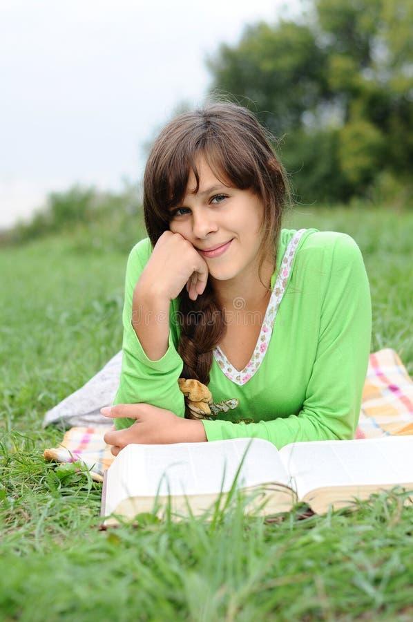 读书的女孩位于在草 库存照片