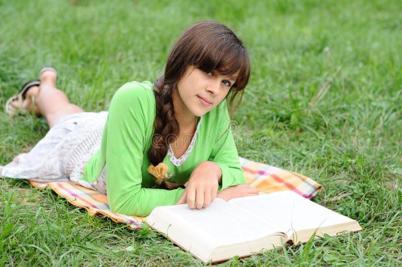 读书的女孩位于在草 免版税库存图片