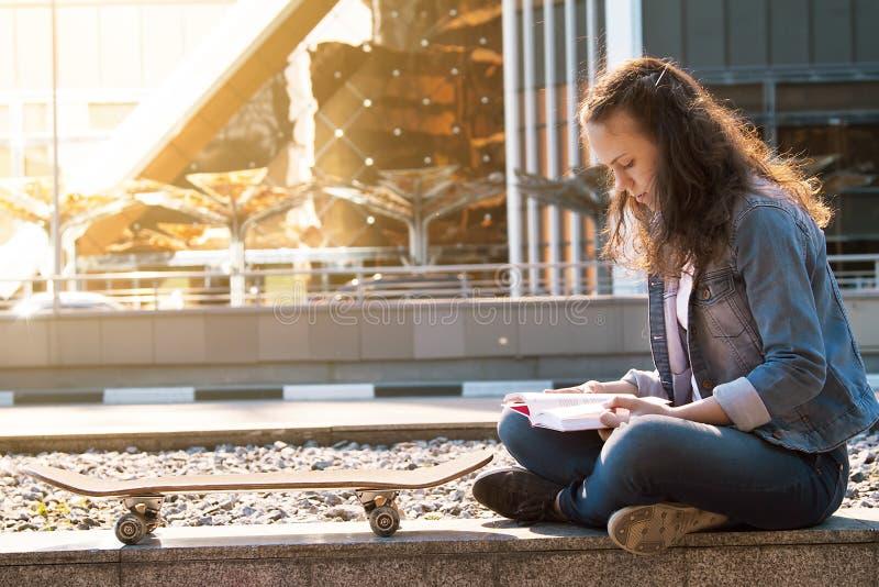 读书的女小学生在街道在大城市 图库摄影