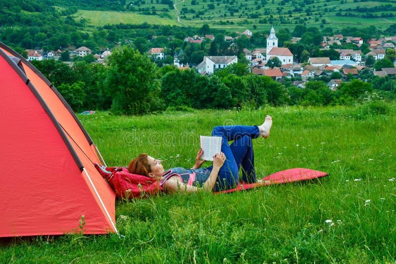 读书的妇女在她的帐篷旁边,当野营在与绿草的小山,在Rimetea村庄上,阿尔巴县,罗马尼亚时 库存照片