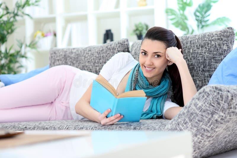 读书的妇女在沙发 免版税库存图片