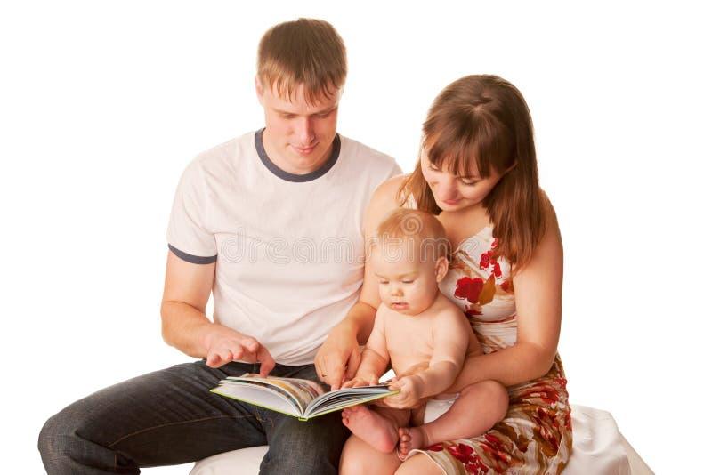 读书的婴孩、母亲和父亲 免版税库存图片