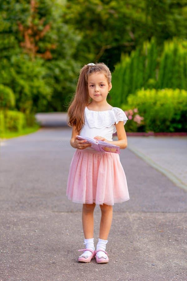 读书的小女孩在街道 教育 免版税库存照片
