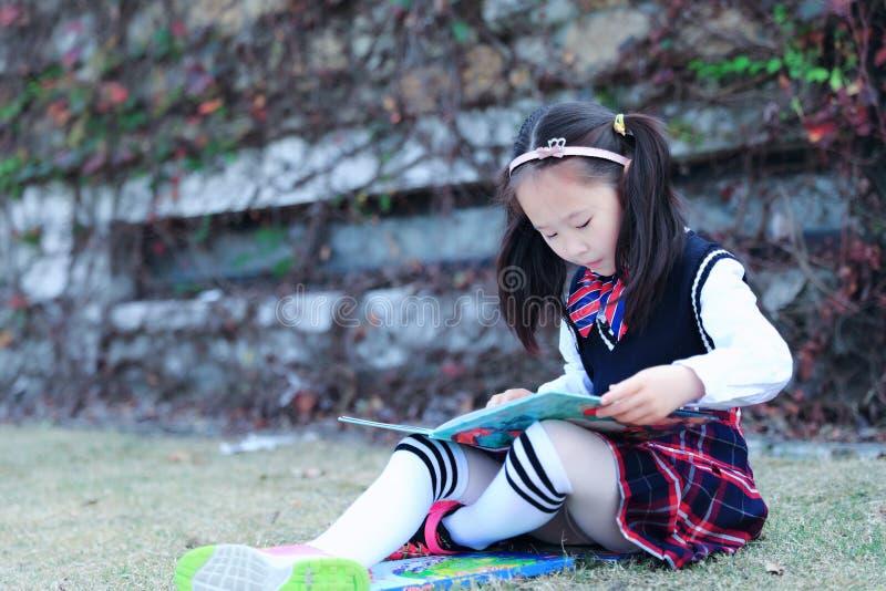 读书的小女孩孩子在草 免版税库存照片