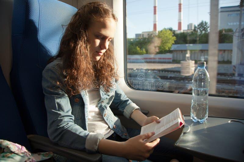 读书的少女,当在火车时 免版税库存图片