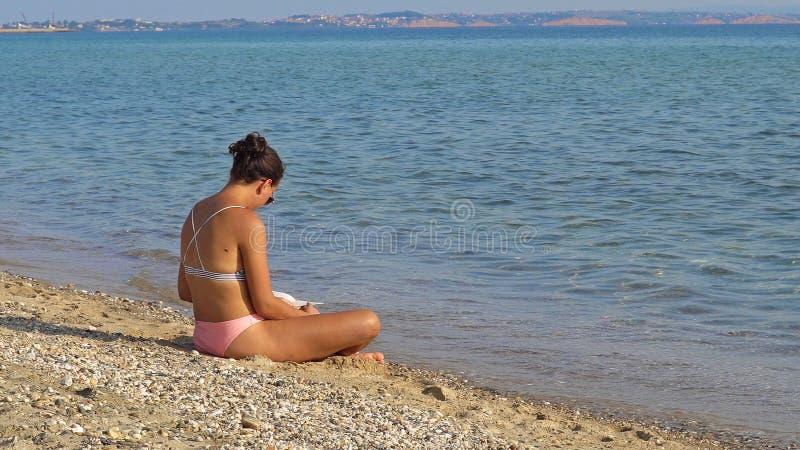 读书的少妇在海滩 图库摄影