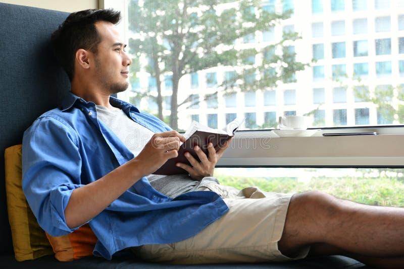 读书的年轻人,当坐沙发时 免版税库存图片