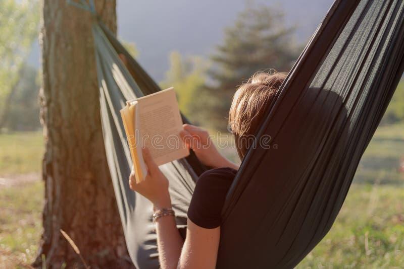 读书的年轻女人在吊床在日落期间 免版税库存图片