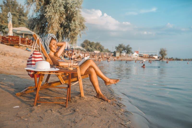 读书的愉快的女孩,当坐轻便折叠躺椅时 免版税图库摄影