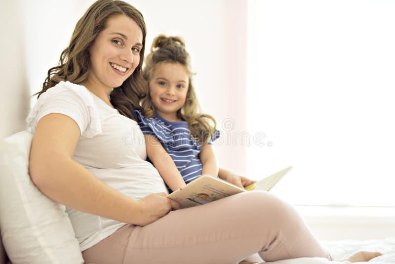 读书的母亲和女儿的画象说谎和放松在床上 图库摄影