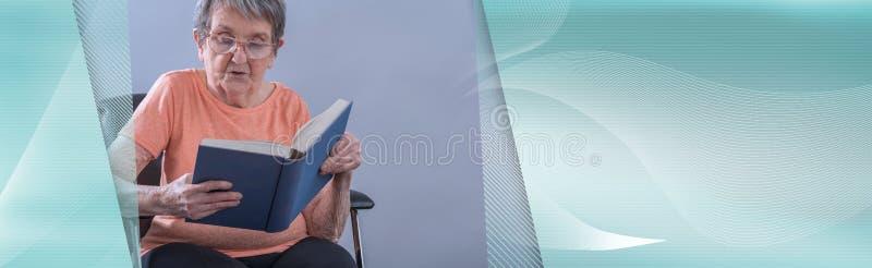 读书的老妇人;全景横幅 免版税库存照片