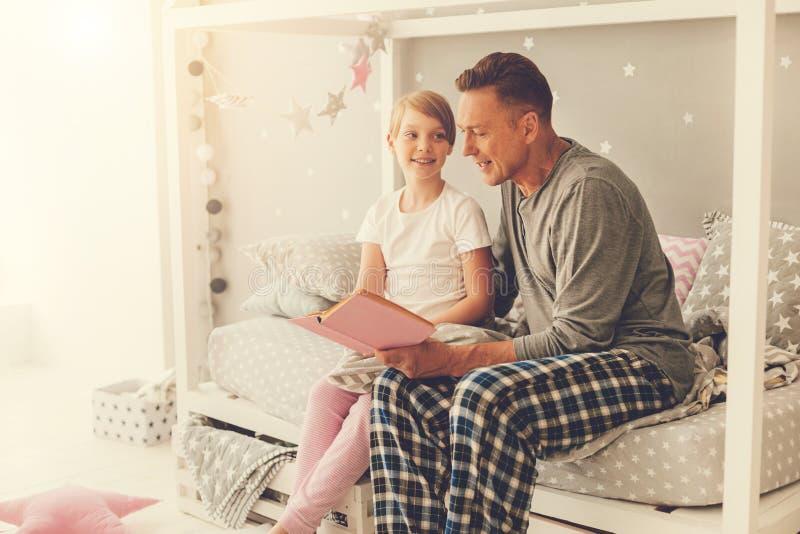 读书的英俊的好人对他的女儿 免版税库存图片