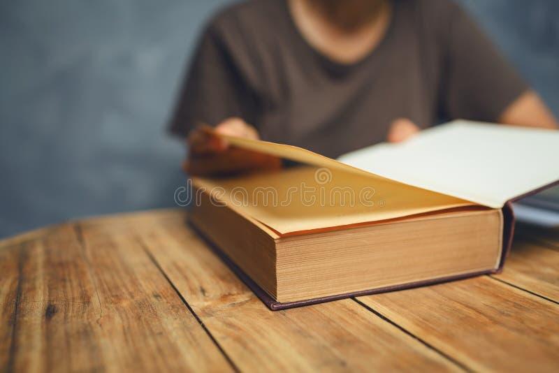 读书的资深妇女在有老葡萄酒tabl的客厅 库存图片