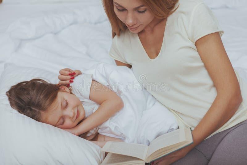 读书的迷人的妇女对她的小女儿 免版税库存图片