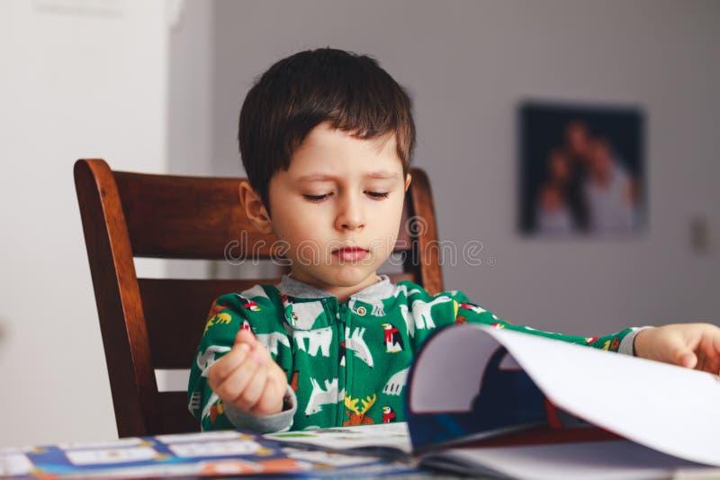 读书的逗人喜爱的男孩,当坐在桌,室内射击上时 李 免版税库存照片