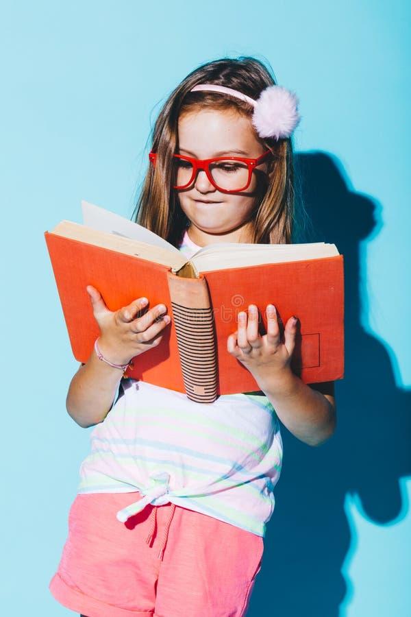读书,佩带的滑稽的红色玻璃的小女孩 免版税库存图片