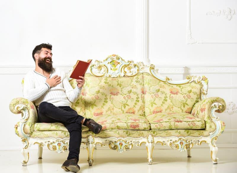 读充满享受的人旧书 有胡子和髭的人坐巴洛克式的样式沙发,拿着书,白色墙壁 免版税库存图片