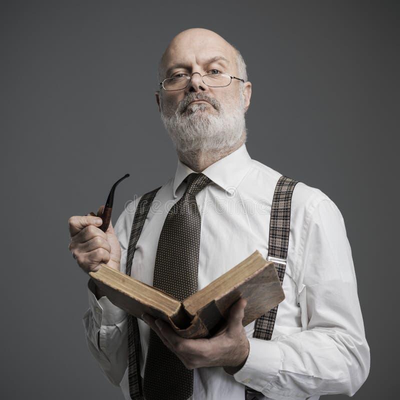 读和抽管子的资深学术教授 免版税库存照片